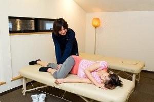 トレーナーが間接の可動域と筋の柔軟性を評価し、体をほぐす
